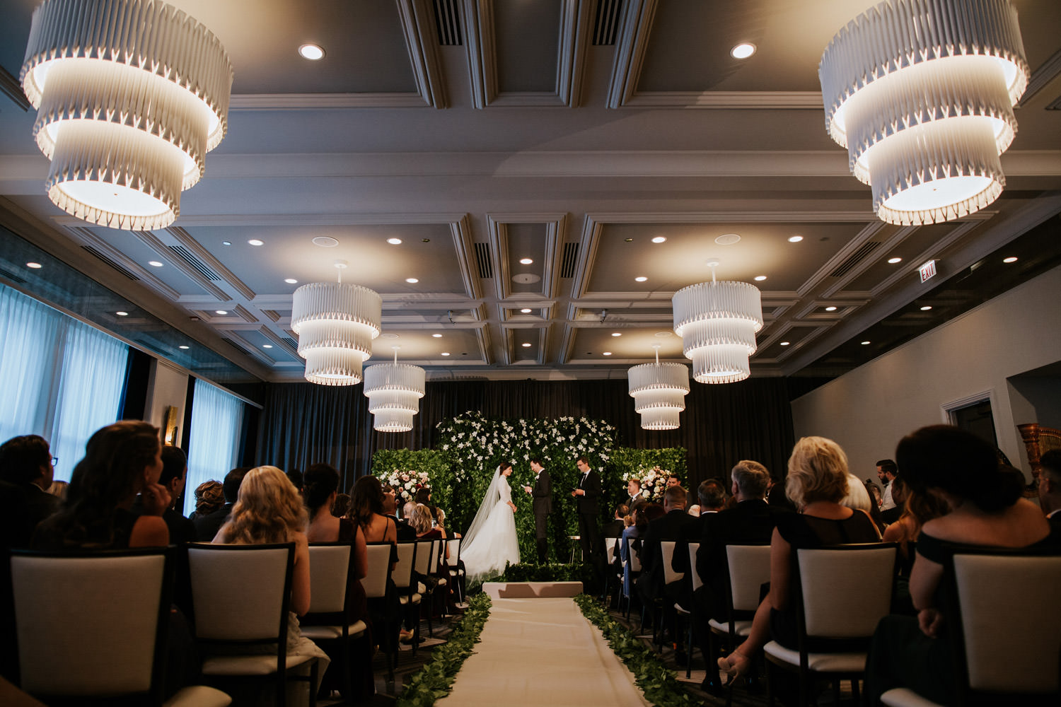Wide shot picture of the wedding ceremony taken inside Hotel Gray