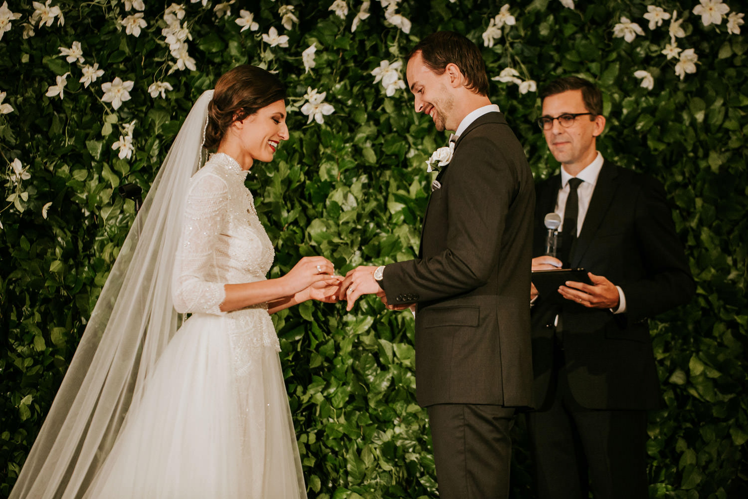 Bride and groom exchange wedding rings during the wedding ceremony in hotel gray chicago