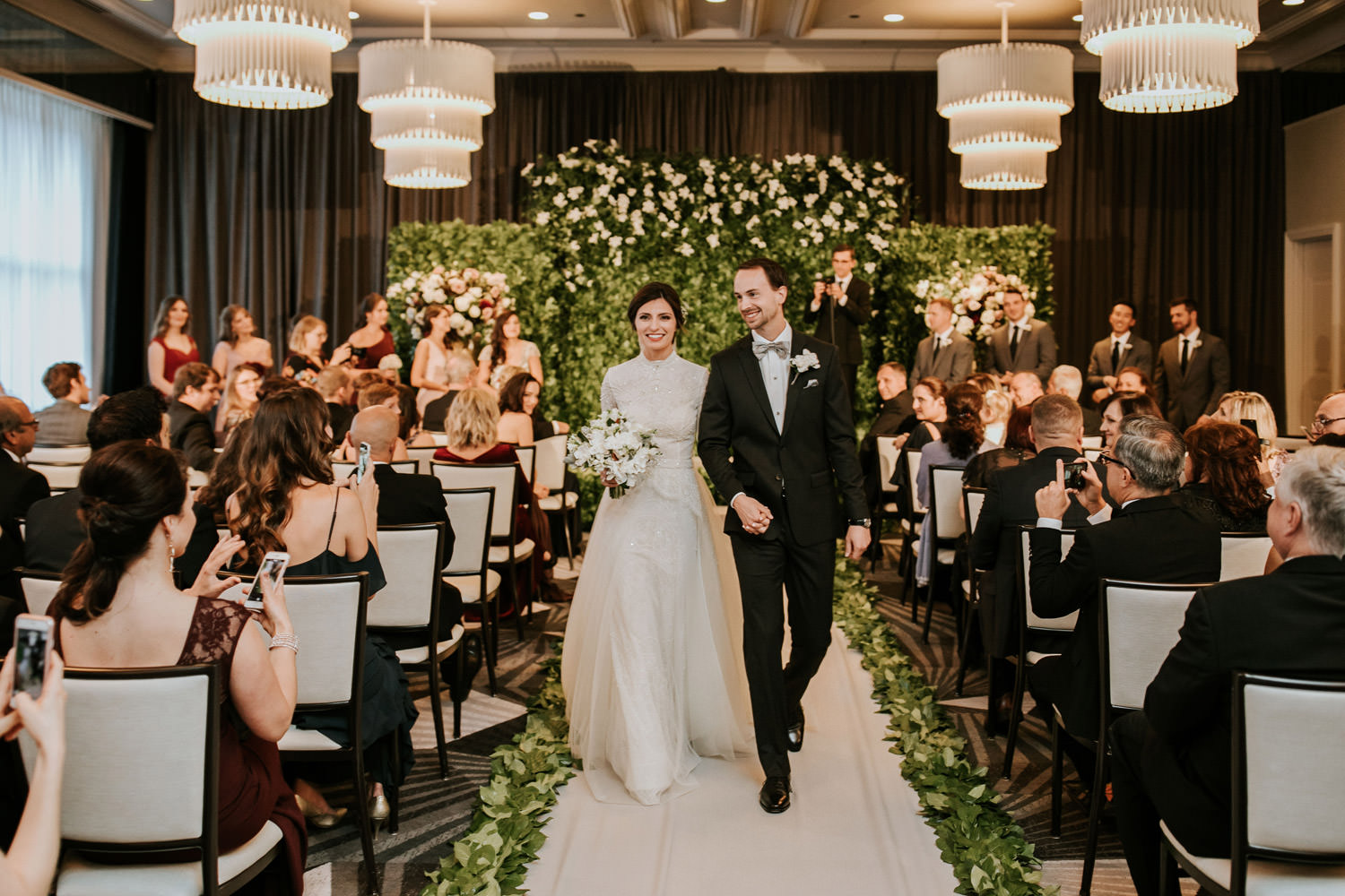Bride and groom walk down the isle after the wedding ceremony at hotel gray in Chicago