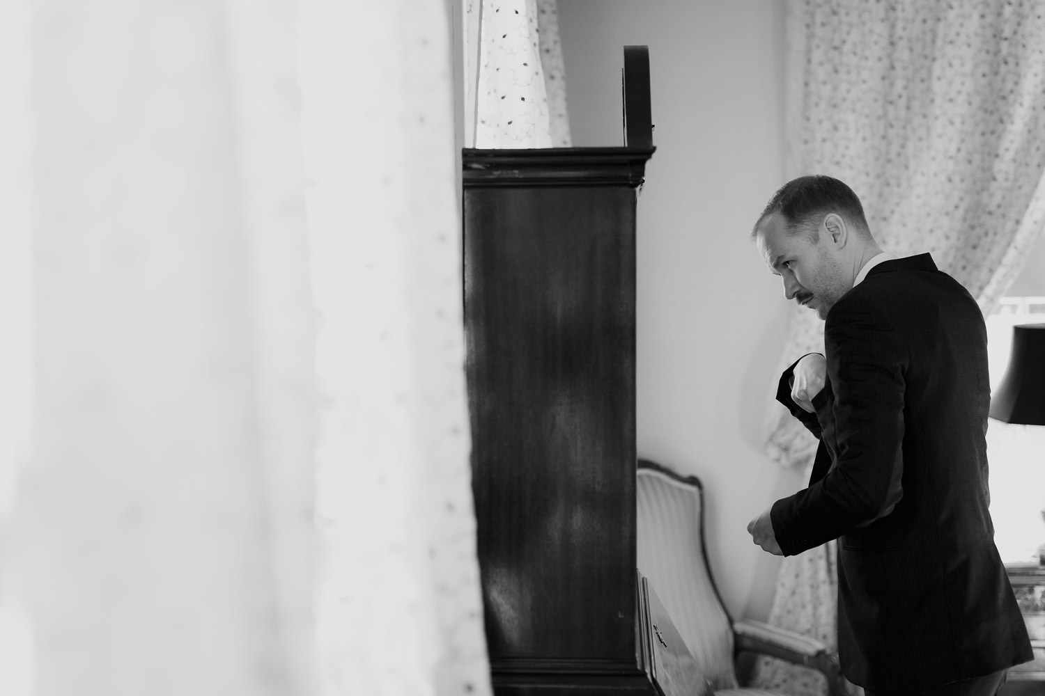 Black and white picture of the groom getting ready in Lake Geneva's Maxwell Mansion