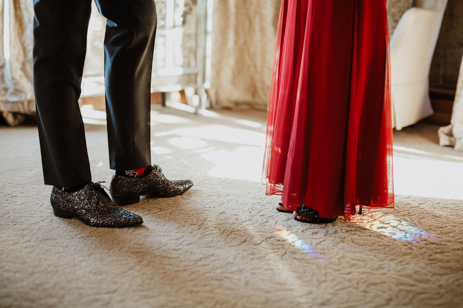 Detail shot of groom's shoot and bride's red dress in Lake Geneva's wedding
