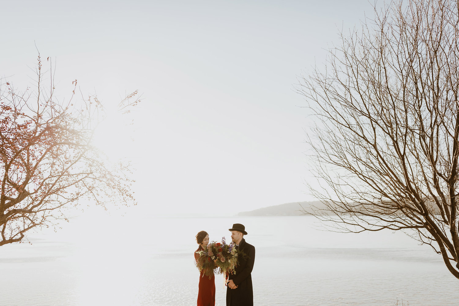 Artistic portrait of the bride and groom take by Lake Geneva on their winter wedding day