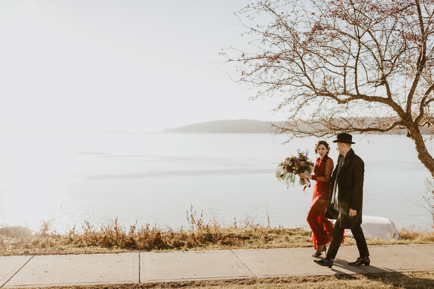 Bride and groom walk along lake geneva in wisconsin on their wedding day