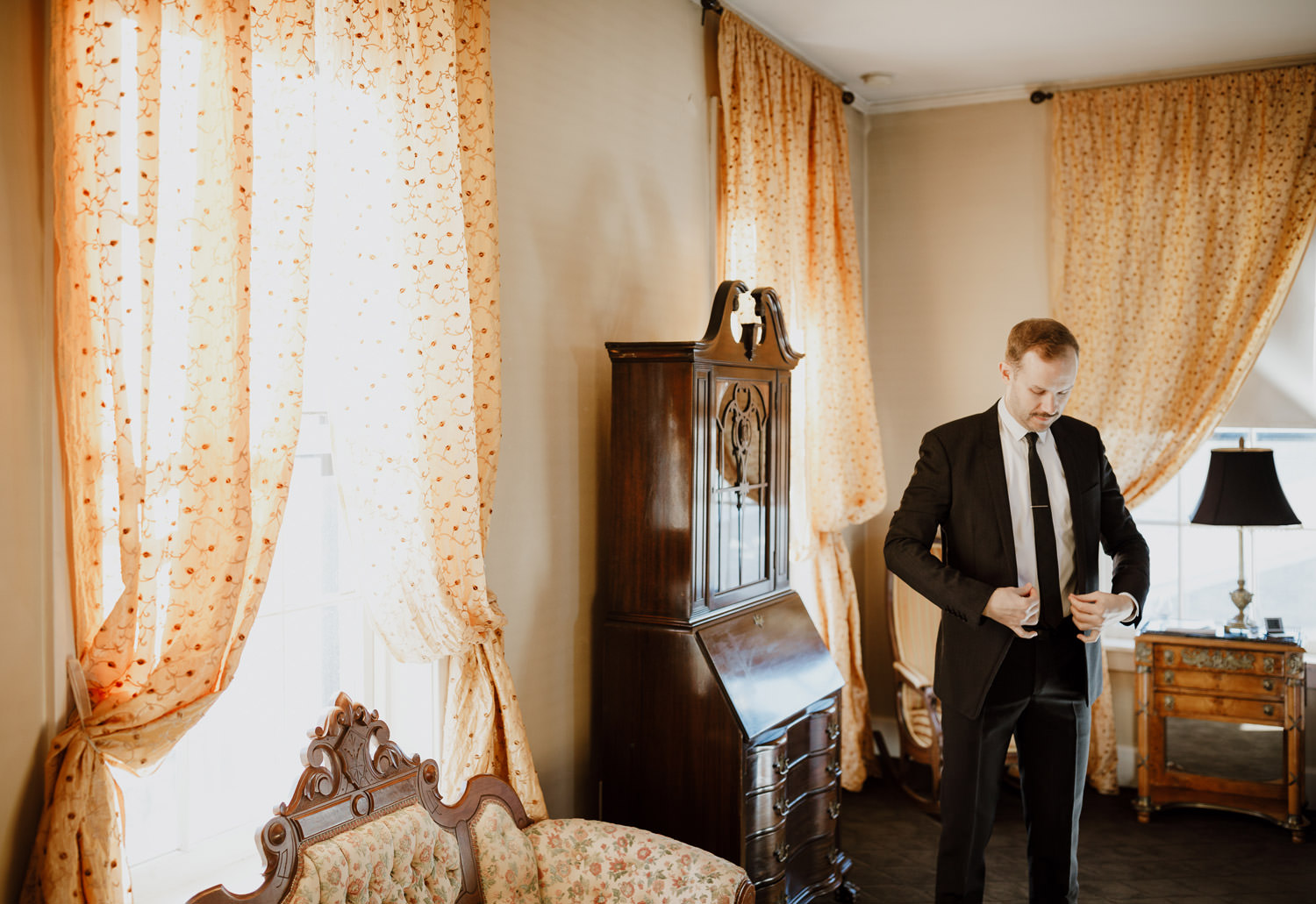 Groom putting on the suit before the wedding ceremony. The shot taken Maxwell Mansion in Lake Geneva