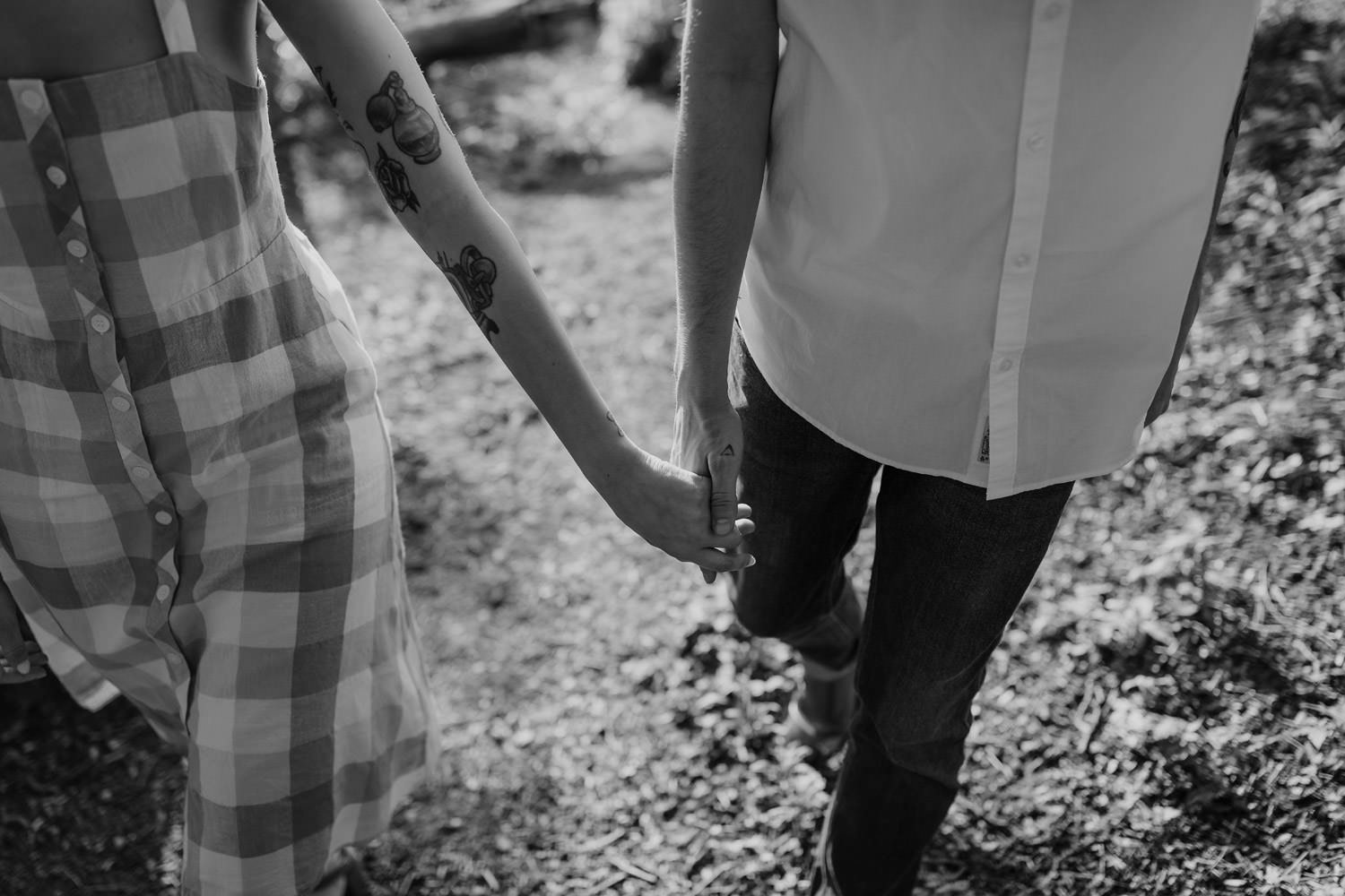 Black and white photograph of a couple walks hand in hand