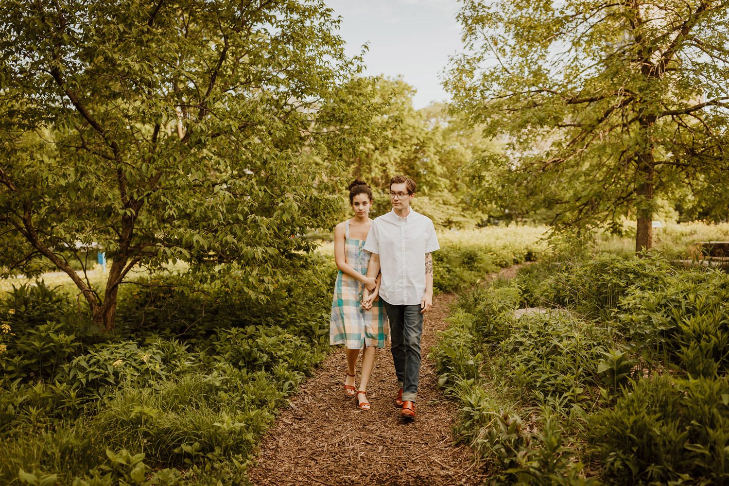 Couple walks on the trail in Lincoln Park. The image taken during their engagement shoot.