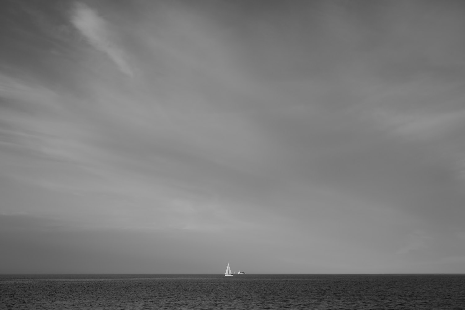 Fine art black and white picture of the Lake Michigan with sailboat in the distance. Photographed at North Ave. beach in Chicago