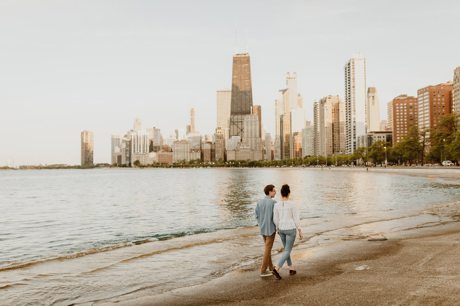 Couple walks toward town town on north ave beach in Chicago. Picture taken during their engagement session