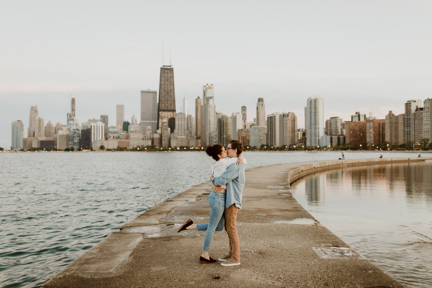 Couple kisses during the engagement session on the pier at North Ave beach in Chicago