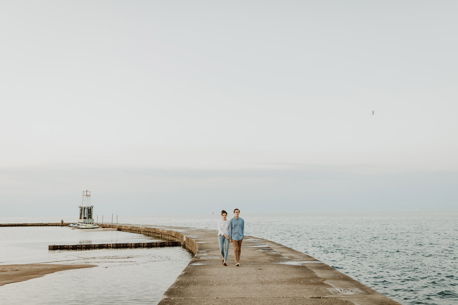 Couple walks down the pier at North Ave beach during their engagement session