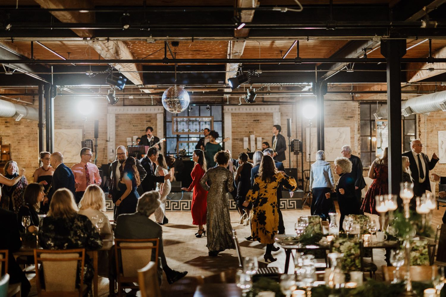 Wide shot of the guests dancing during the wedding inside the Salvage One in Chicago