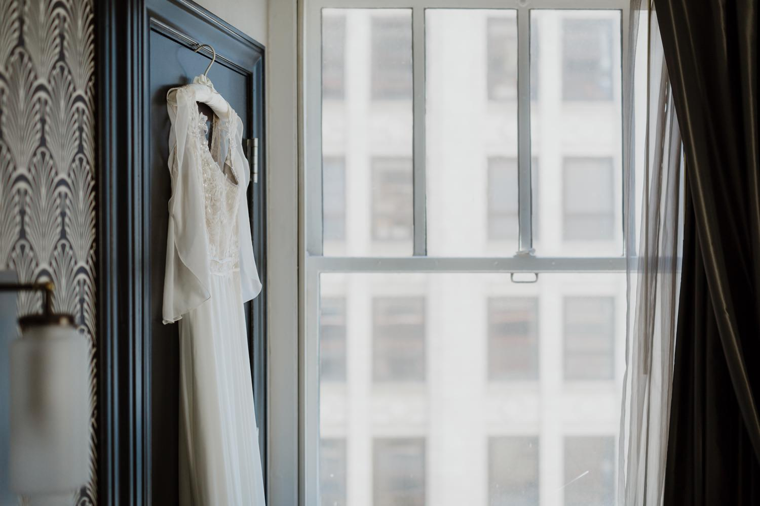 Picture of the wedding dress hanging inside the room of Allegro Hotel in Chicago