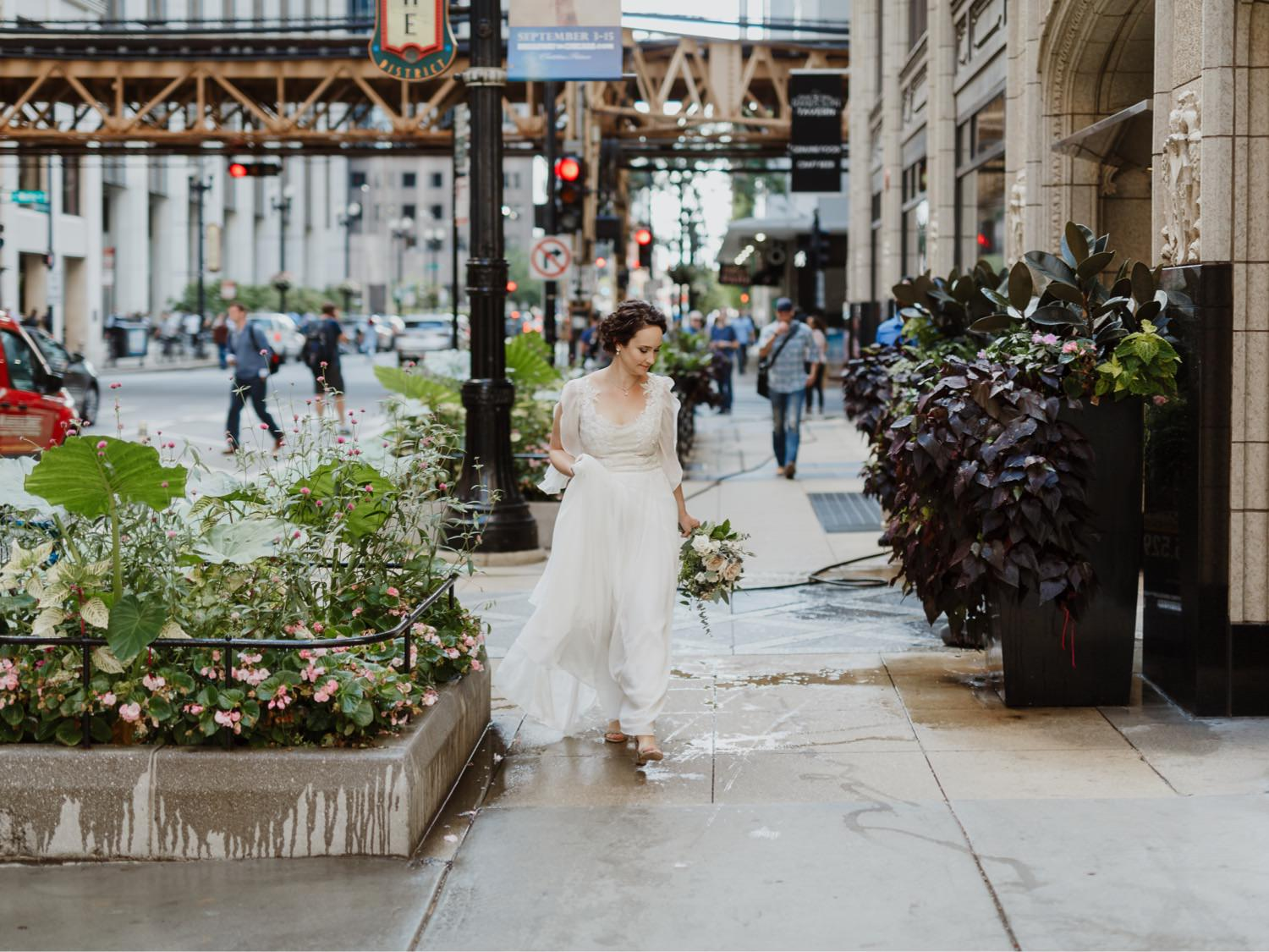 Bride walks in downtown Chicago to see the groom for the first time across from Allegro hotel in Chicago