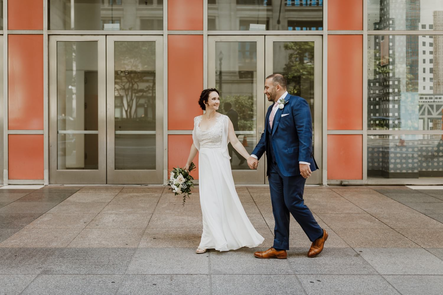 Bride and groom walk on the street of downtown Chicago during their fall wedding day