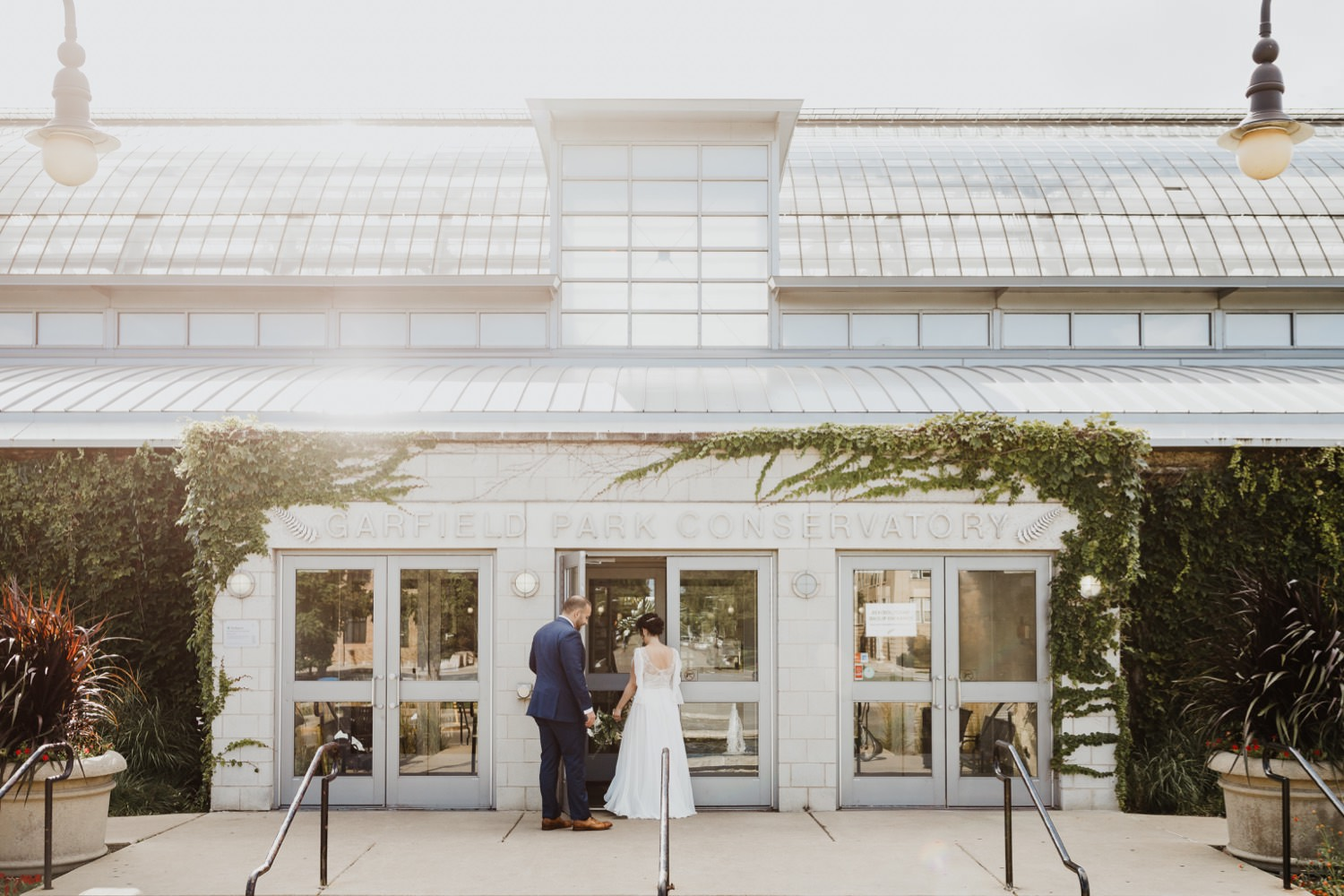 bride and groom walk toward Garfield Park Conservatory