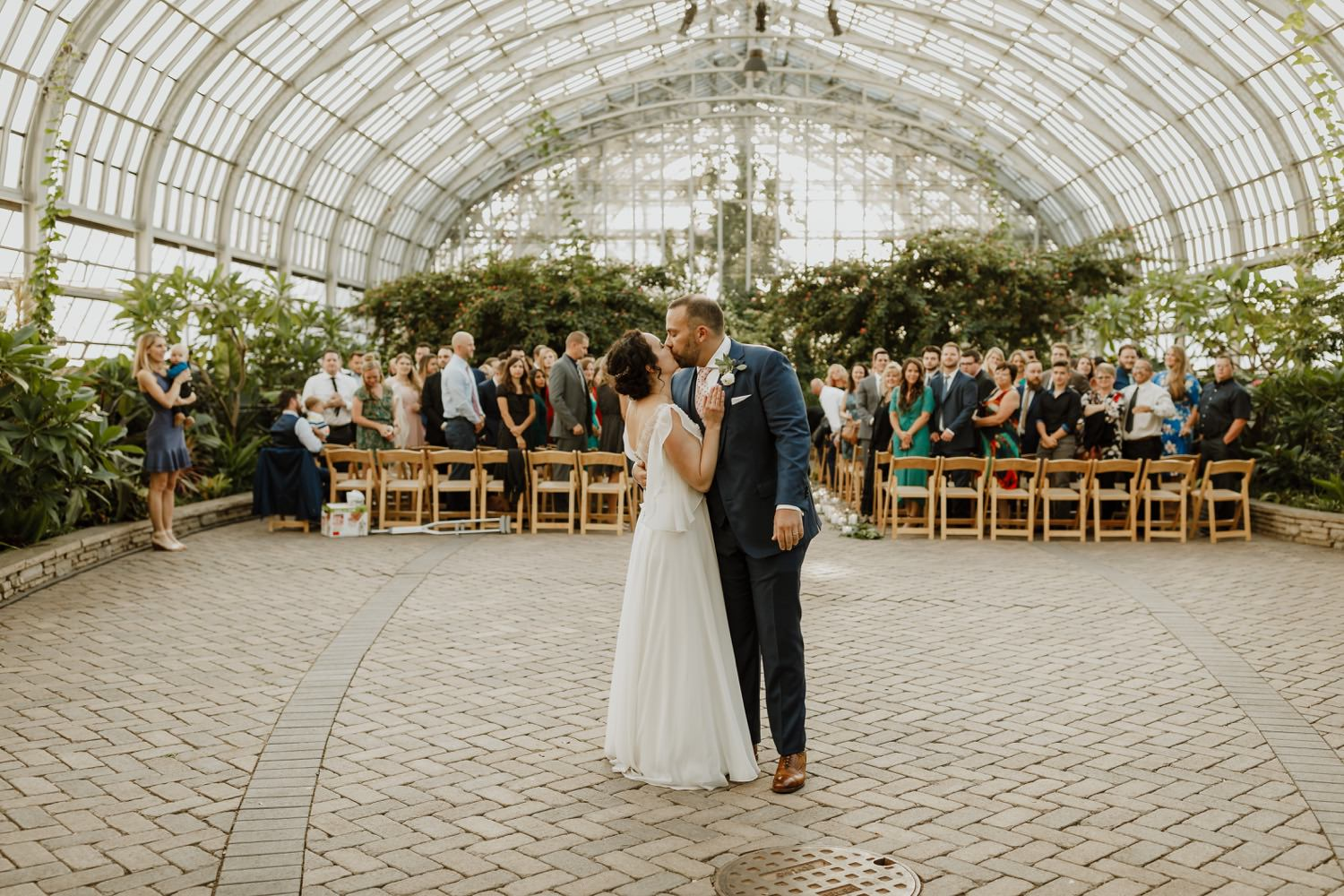 Garfield Park conservatory wedding. Bride and groom kiss after the ceremony.