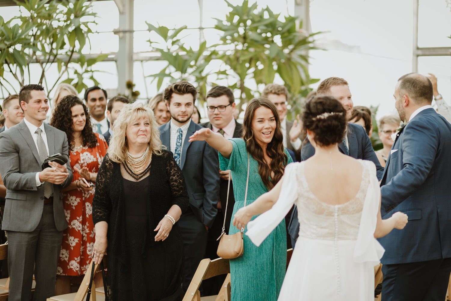 Guests and family hug the bride after the wedding ceremony at Garfield Park conservatory