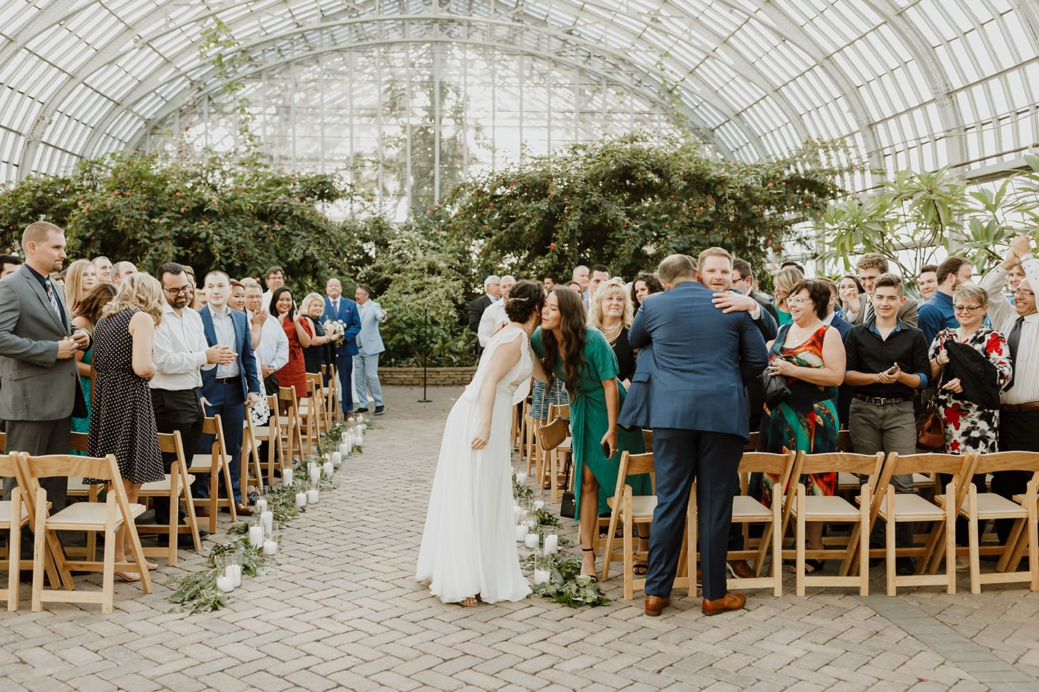 guest cheer and hug bride and groom at Garfield Park conservatory wedding