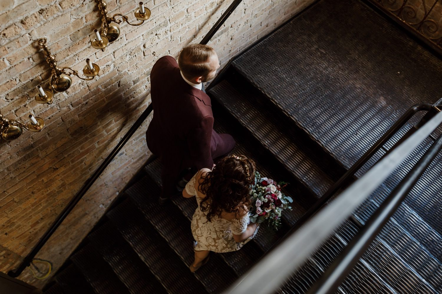 Bride and groom walk up the stairs inside the salvage one. Taken during the wedding day in December.