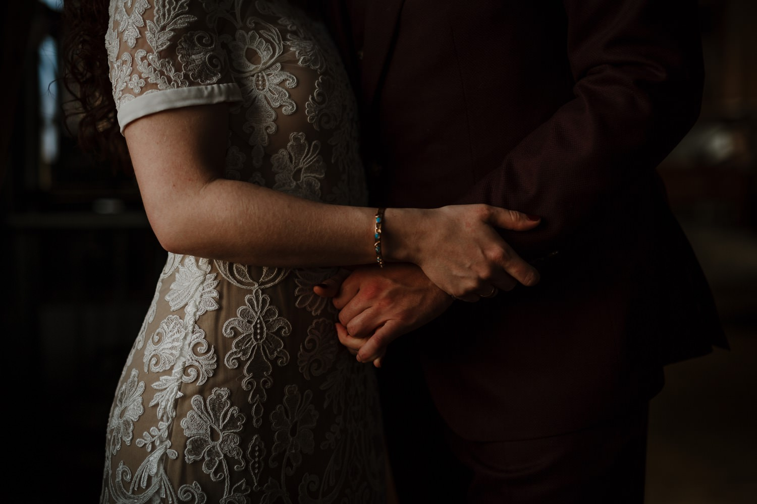 Bride and groom embrace their hands at salvage one during the portrait shoot