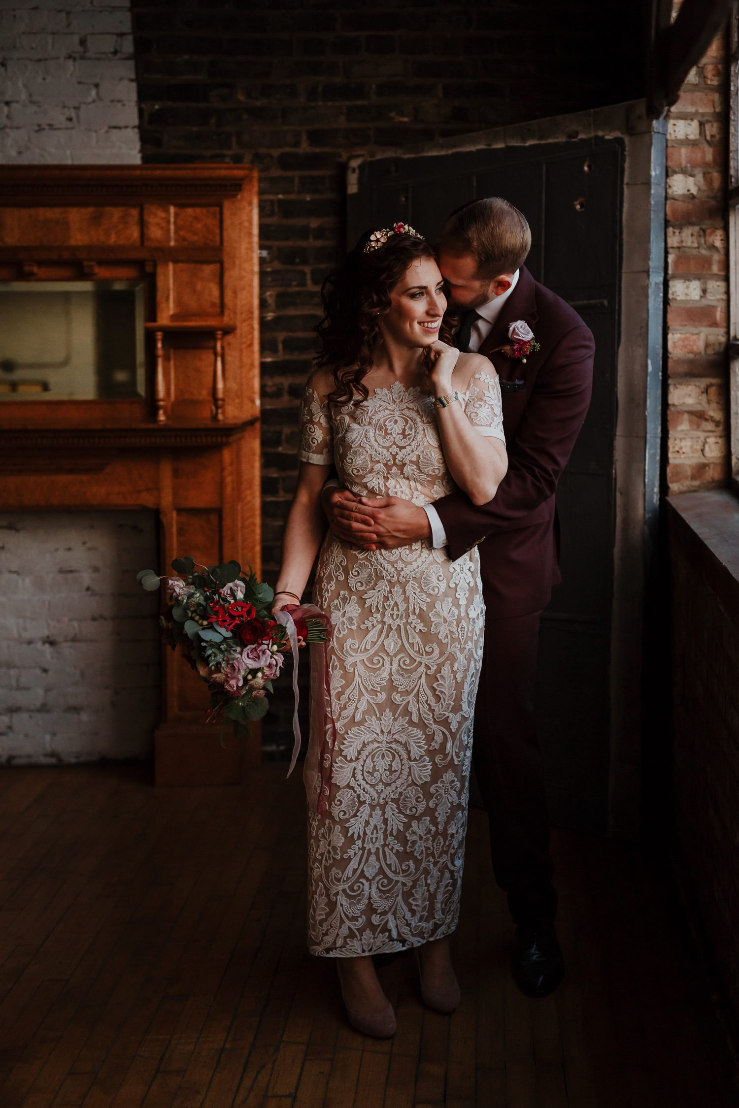 Groom embraces his bride during the portrait shoot at Salvage One