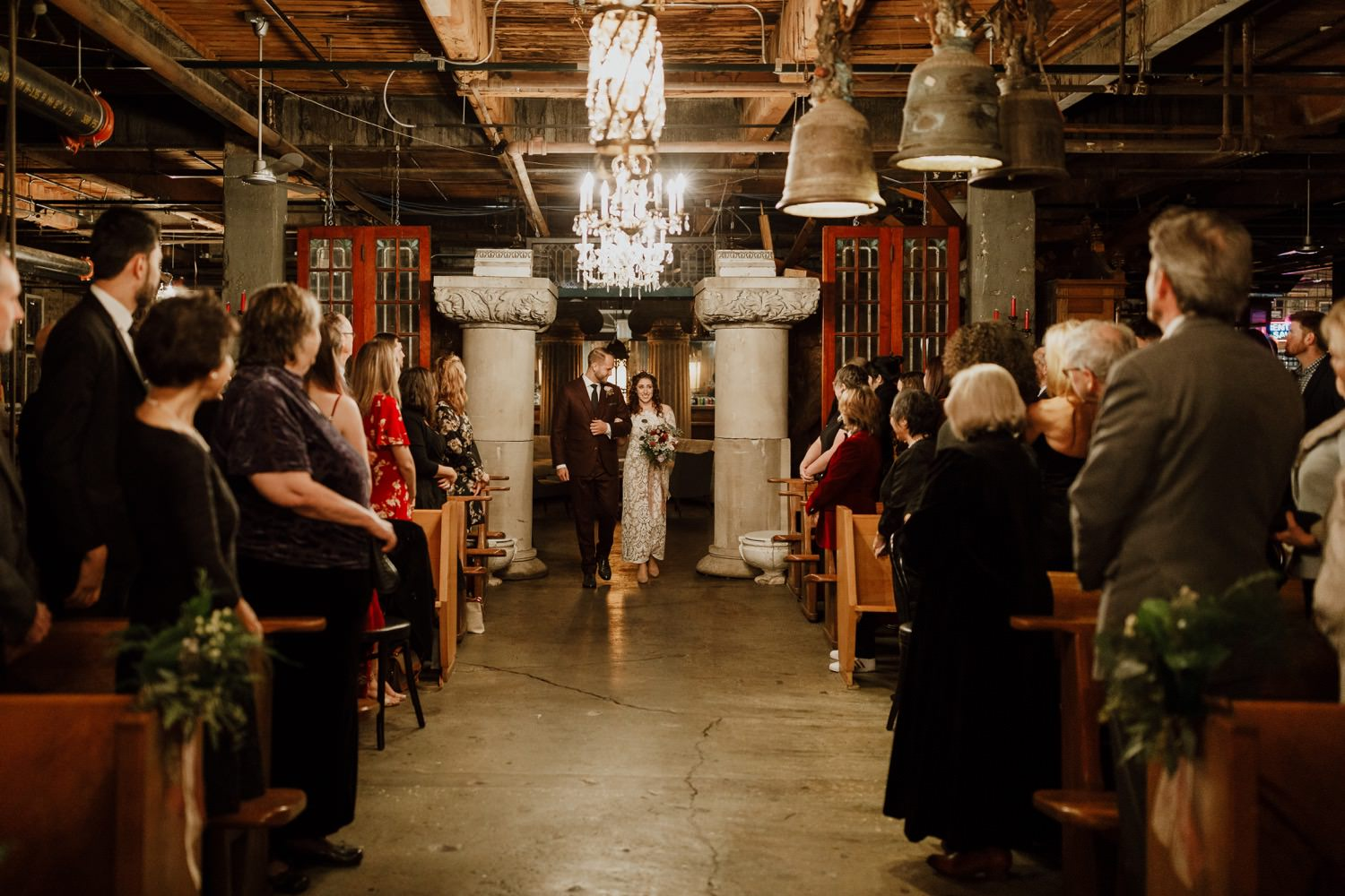Bride and groom walk down the isle during the ceremony at Salvage One