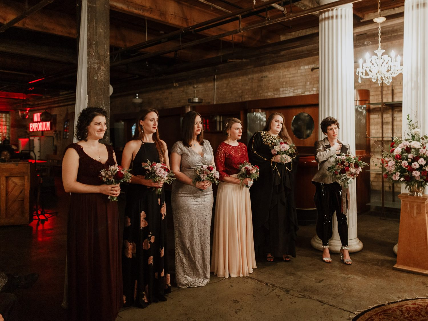 Bridal party looks at the bride and groom during the ring exchange at salvage One Chicago