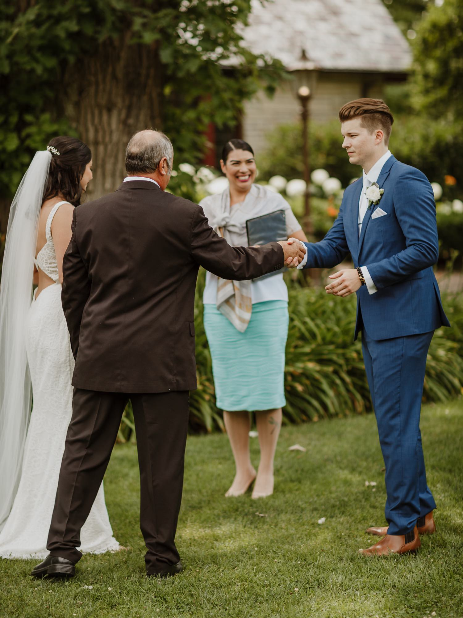 Groom shakes hands with the father of the bride at the wedding ceremony at Redfield Estate