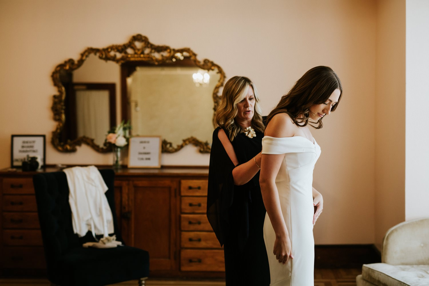 Mother of the bride helps the bride put on her dress at the Haight in Elgin