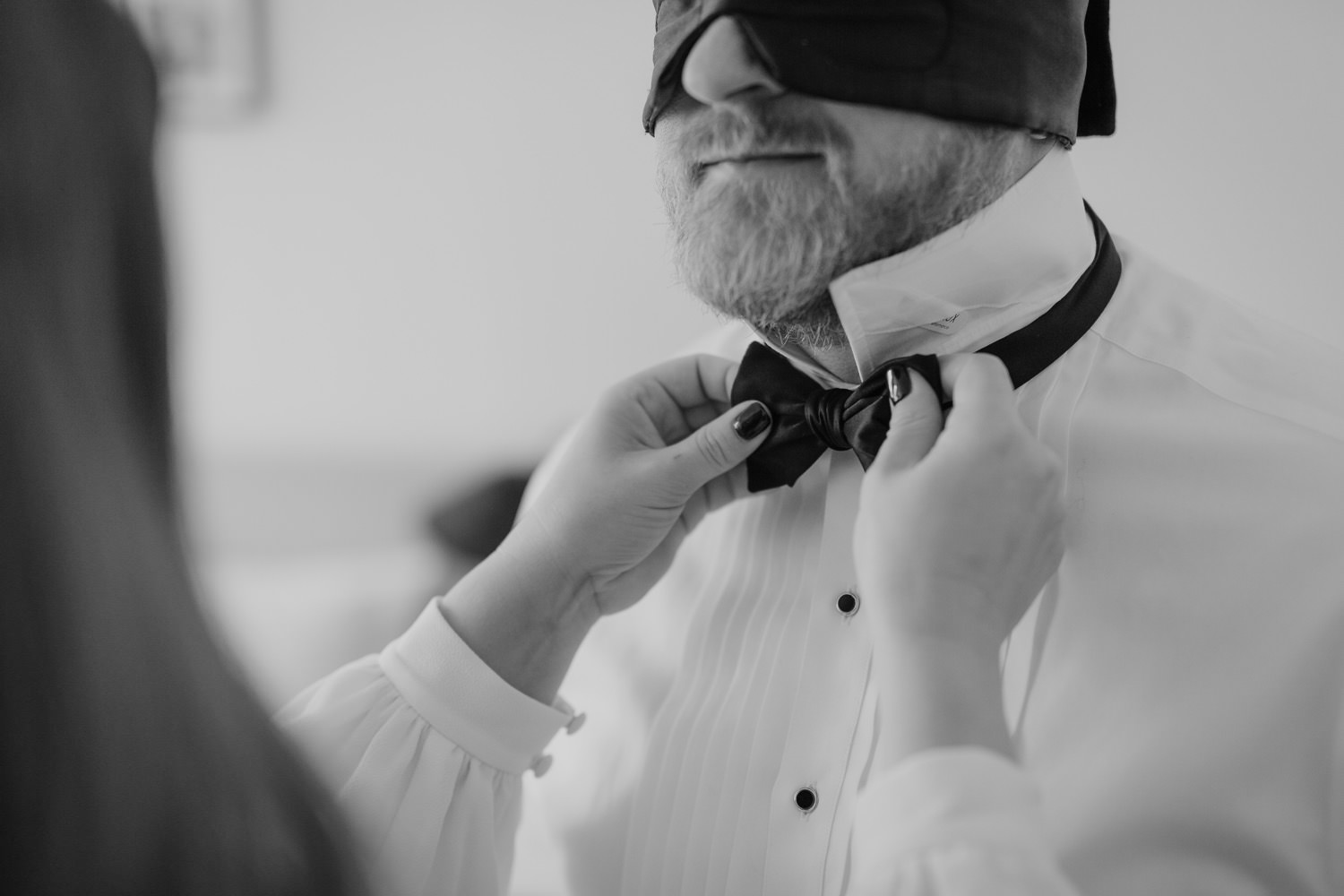bride helping the groom get ready on the elopement day
