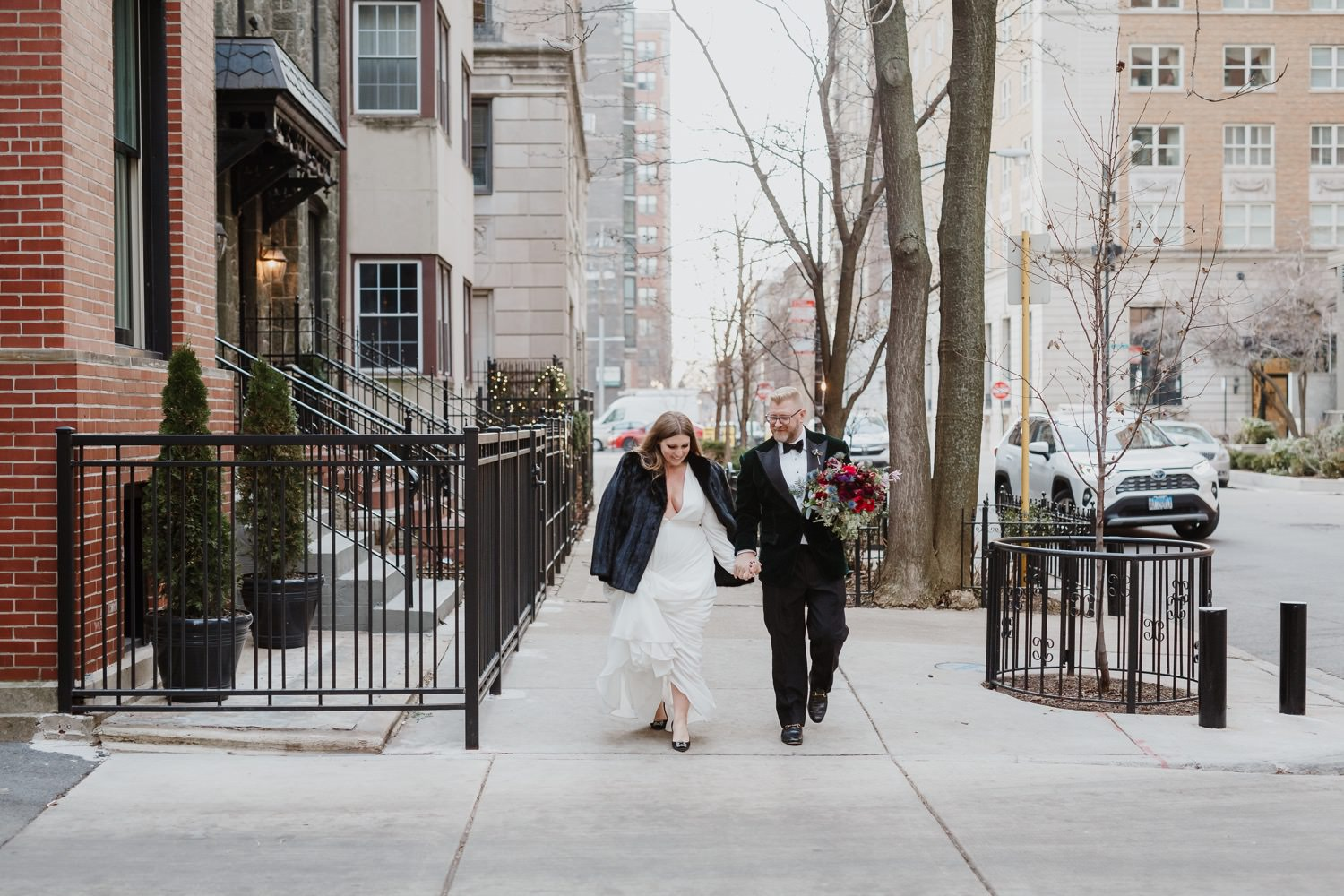 bride and groom walk in downtown street during their Chicago elopment