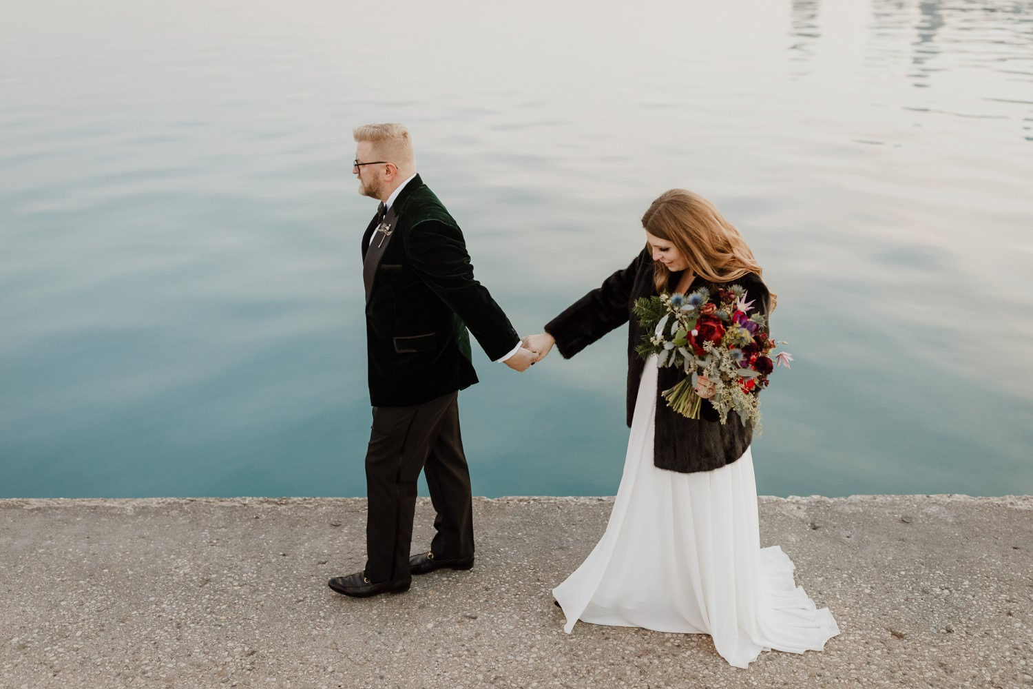 bride and groom walk along the north ave beach on their elopement day