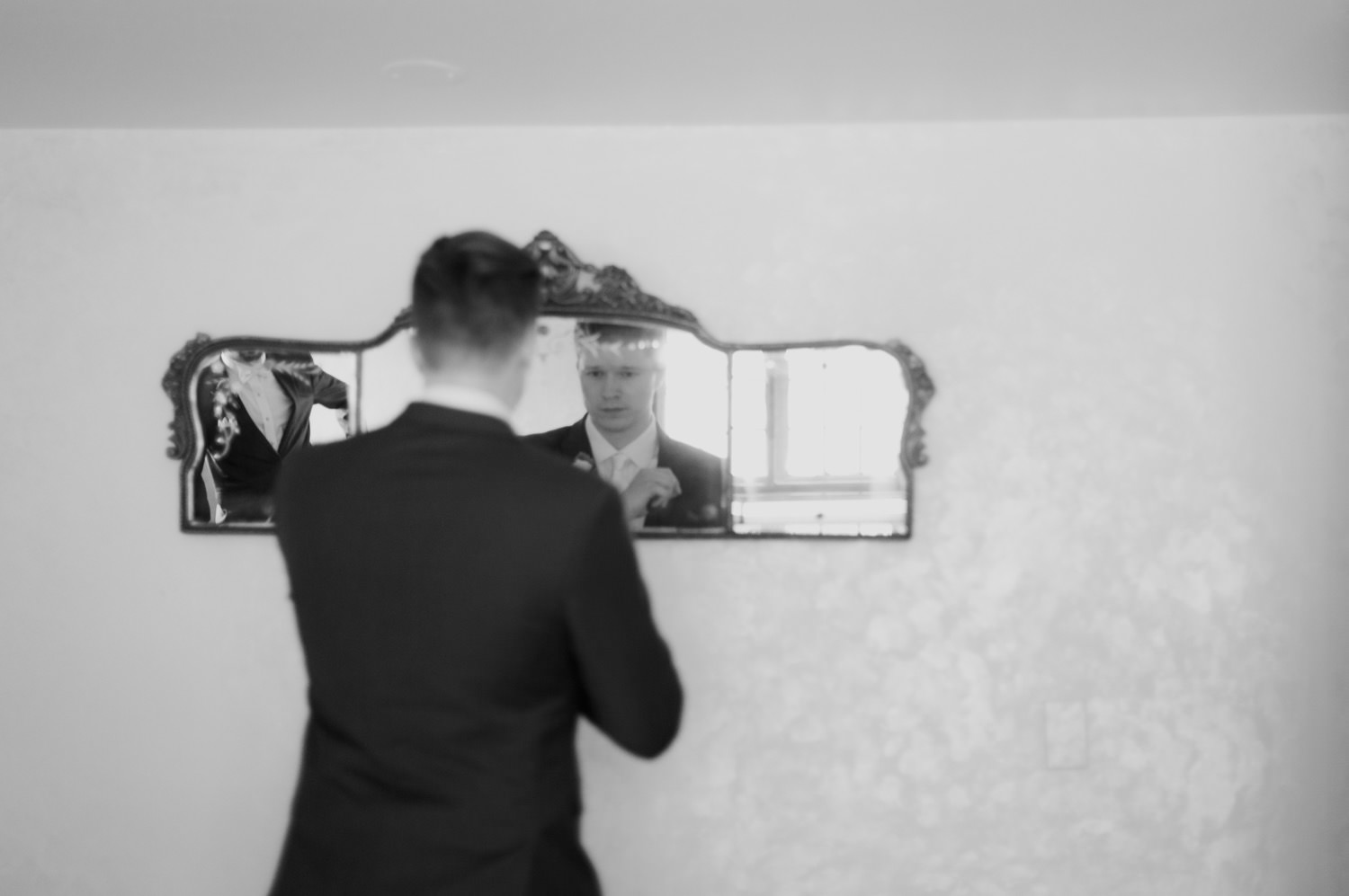 groom lookin into the mirror while getting ready at redfield estate
