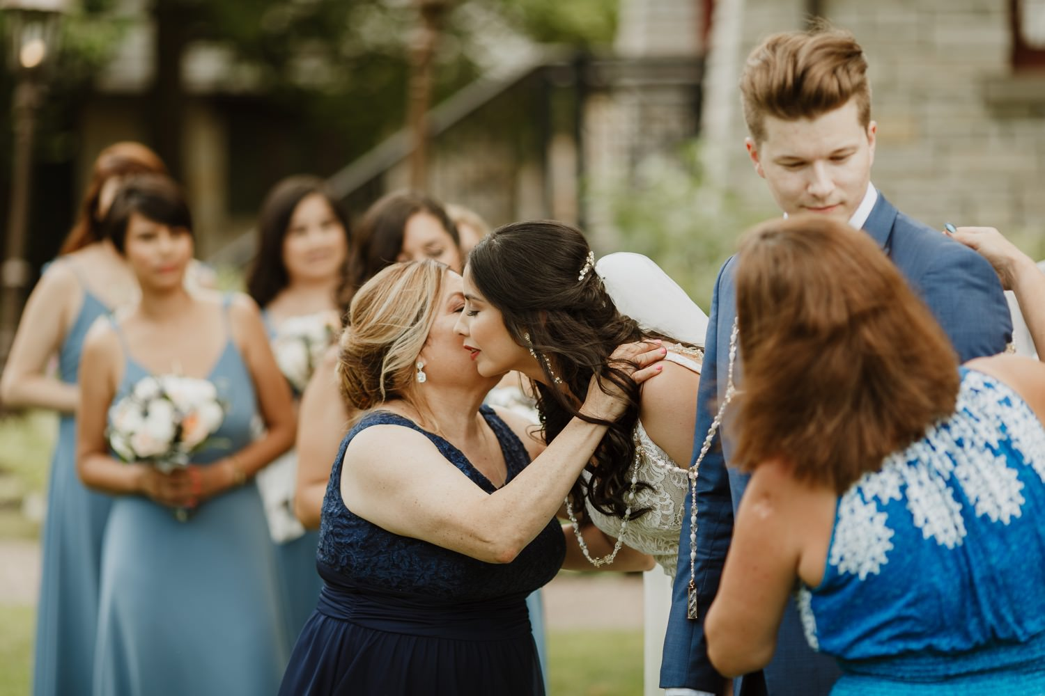 Bride kisses her mother during the wedding ceremony at Redfield Estate