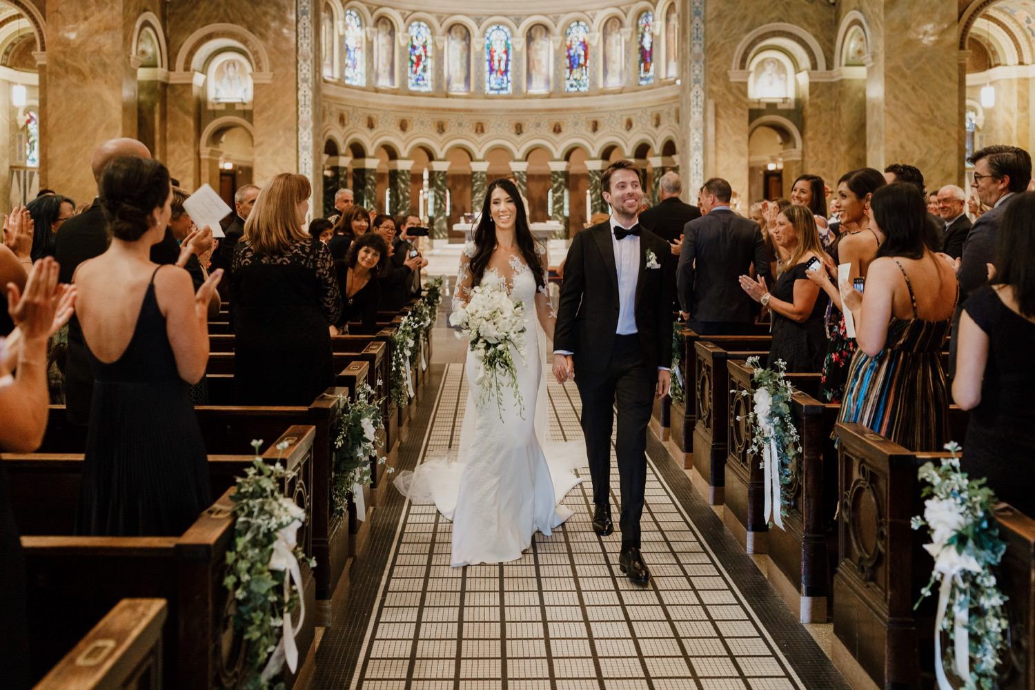 Bride and groom recess down the isle on their wedding day in St. Clement Church in Chicago