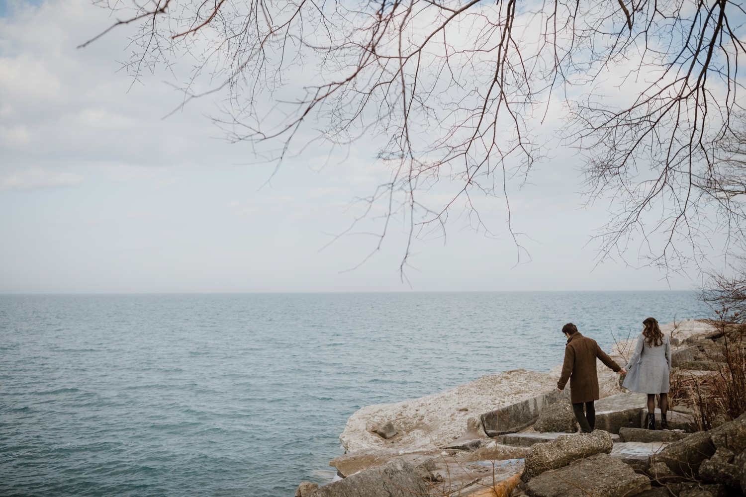 Couple walks by lake Michigan near Northwester University during their engagement photos