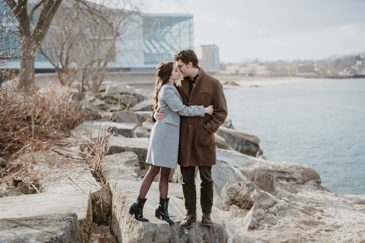 Photo with a couple kisses during the engagement session with Northwestern University in the background.