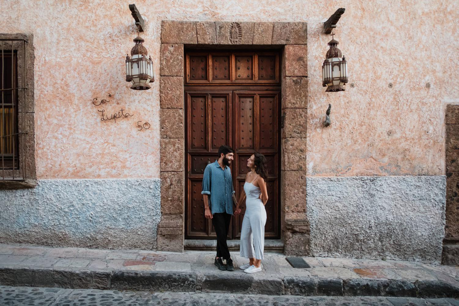 A couple standing in front of the large, old, wooden door in San Miguel de Allende